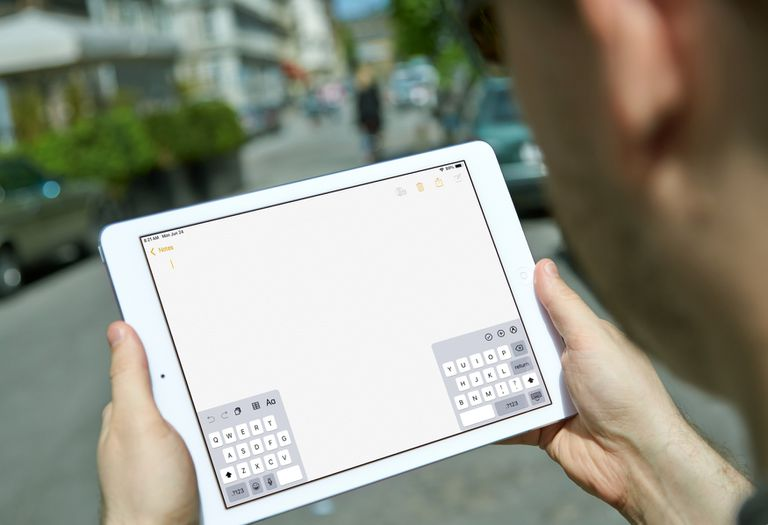 A man using an iPad with its on-screen keyboard split into two parts.