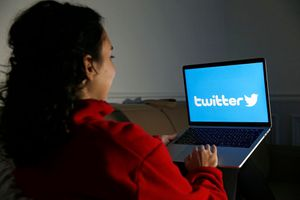 Someone looking at a laptop with the Twitter logo displayed on the screen.