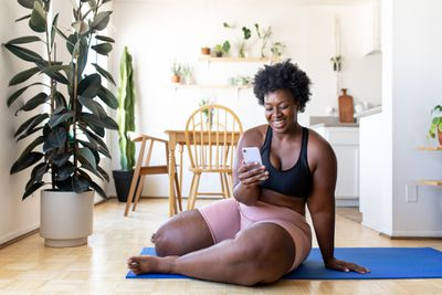 A woman sitting on the floor in fitness gear smiling at her smartphone