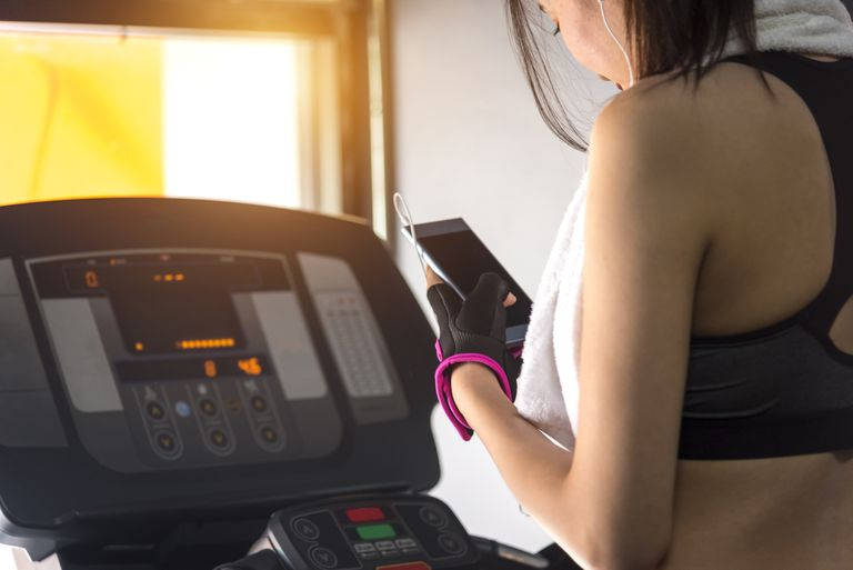 Woman on a treadmill looking at her phone