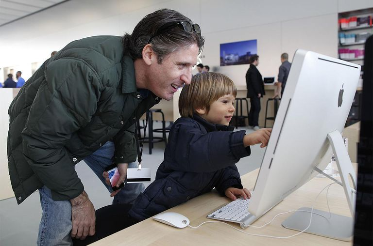 Apple employee Jason Roth (L) and his son Tyler Roth, 3, play with an iMac