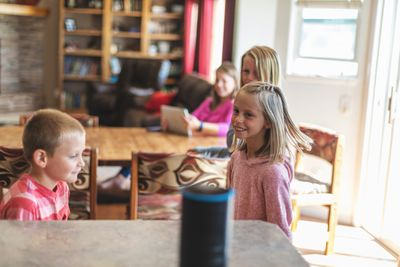 Kids using a smart home assistant in the kitchen.