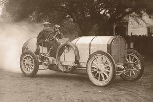 Two men driving race car (B&W sepia tone)