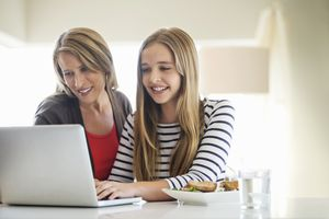 Mother and daughter using laptop together looking at Facebook with privacy settings