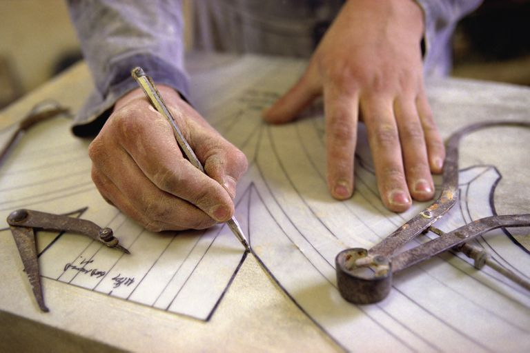 Photograph depicting a stone mason using a template to trace architectural flourishes.