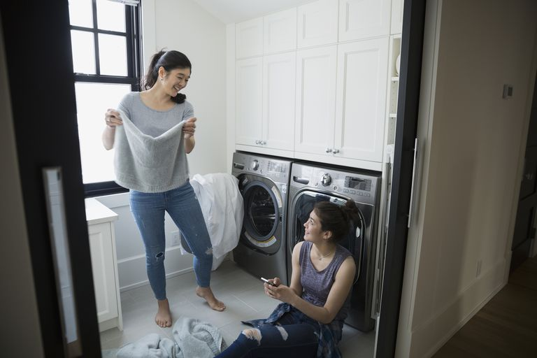 Mother and daughter using smart washing machine