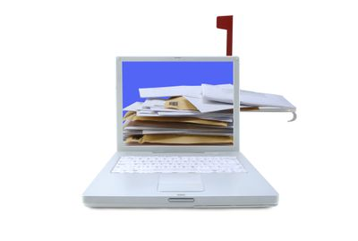 Paper envelopes protruding from laptop screen; mailbox flag up
