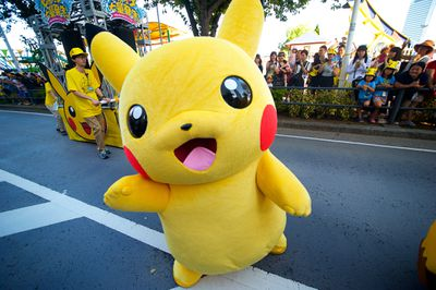 A person in a Pikachu costume marches in a parade.