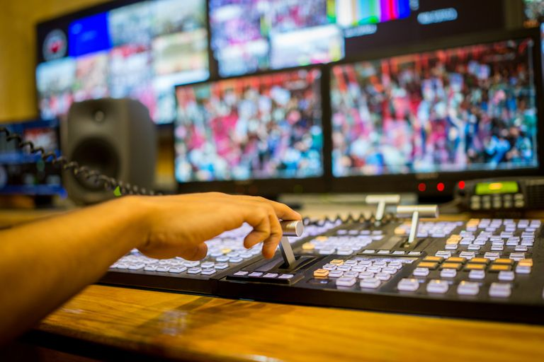 An image of a person working at a video editing board in a newsroom.