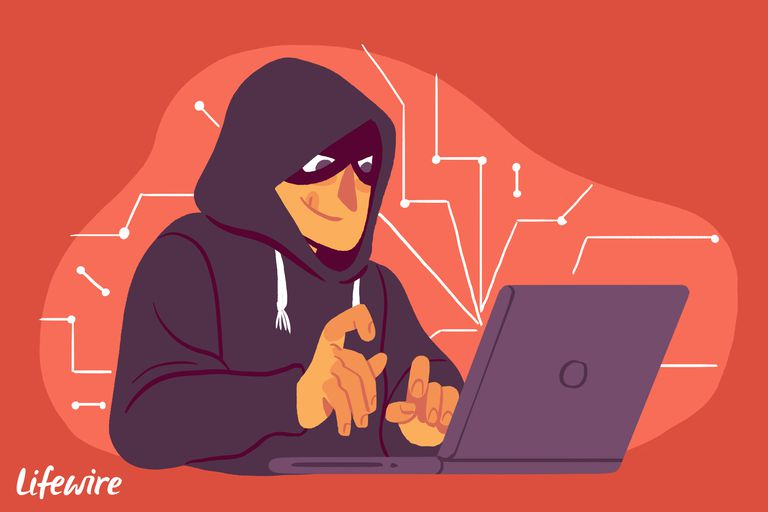 Criminal in a hoodie and a mask at a laptop