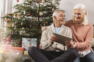 Senior couple looking at a tablet computer in front of Christmas tree