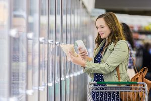 A woman using a smartphone while grocery shopping