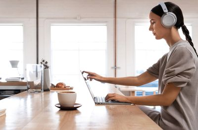 A woman wearing Surface Headphones while using a Surface Laptop in her kitchen.