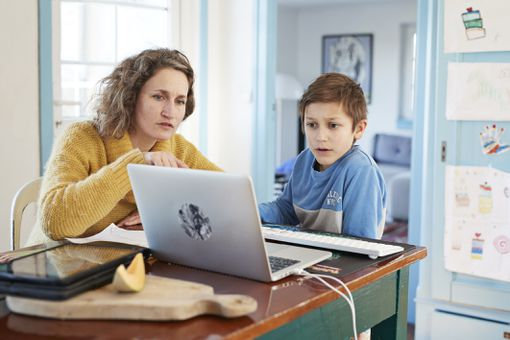 Mother homeschooling son on a laptop