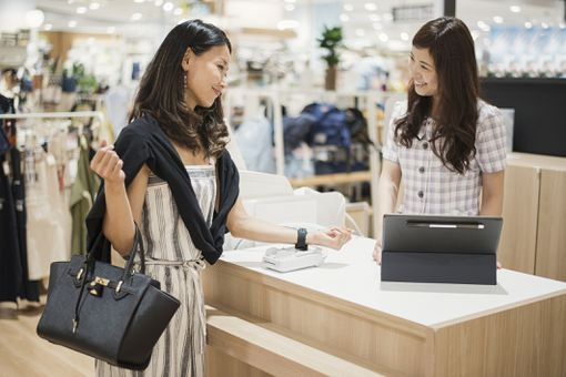 Woman contactlessly paying for purchase with smartwatch