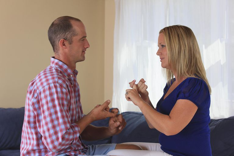 Picture of a man and women communicating with sign language