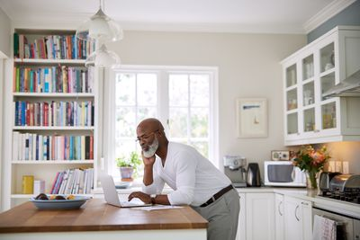 A man standing at a kitchen table looking at his laptop