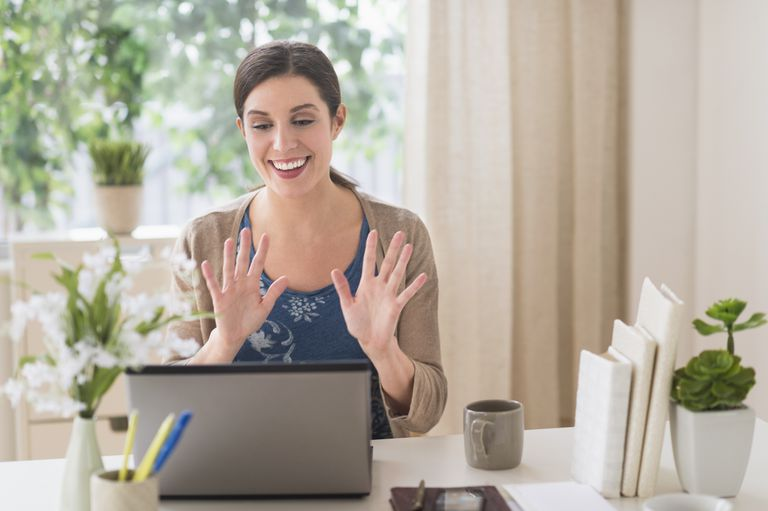 Woman waving at her computer in a home office