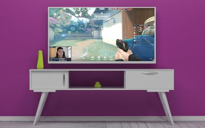 A Twitch stream playing on a TV in a purple room.