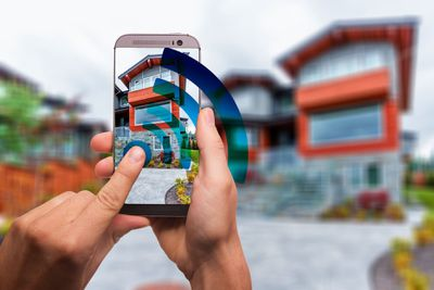 A person using a smartphone to snap a photo of a house.