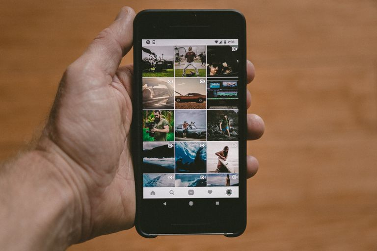An image of a man holding a smartphone and browsing an Instagram profile.