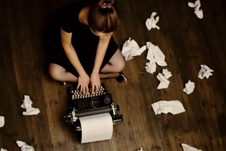 Woman typing surrounded by discarded sheets