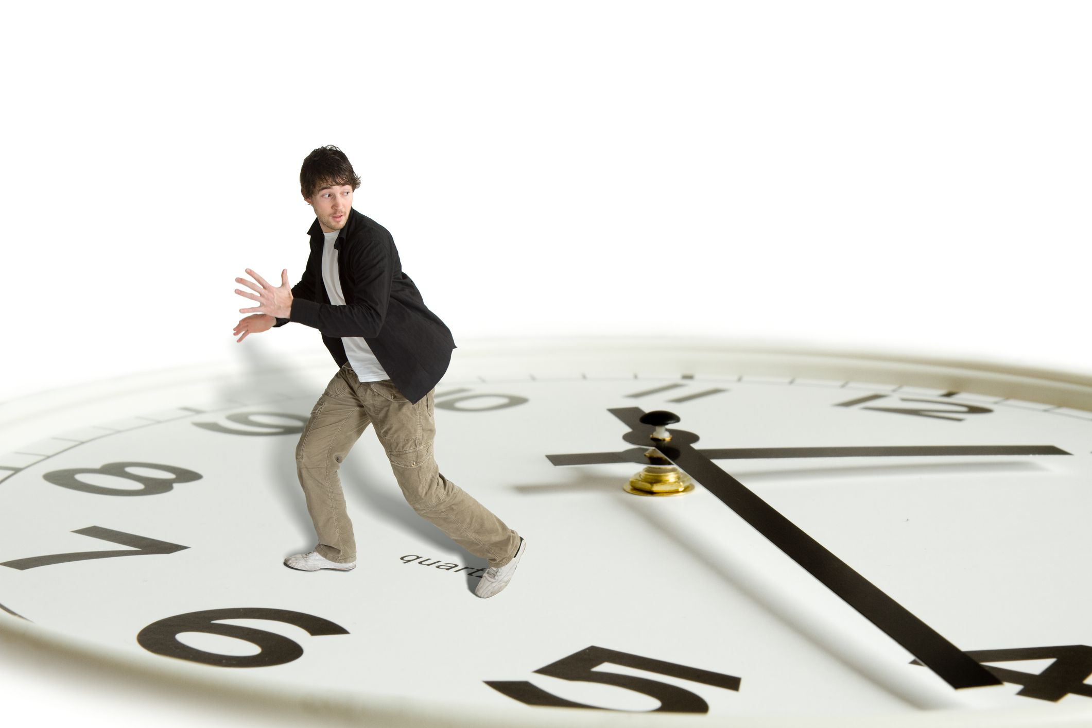 Person on a huge clock face running away from the hands