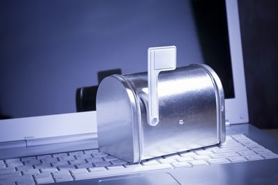 You've Got Mail. Miniature silver mailbox on white laptop