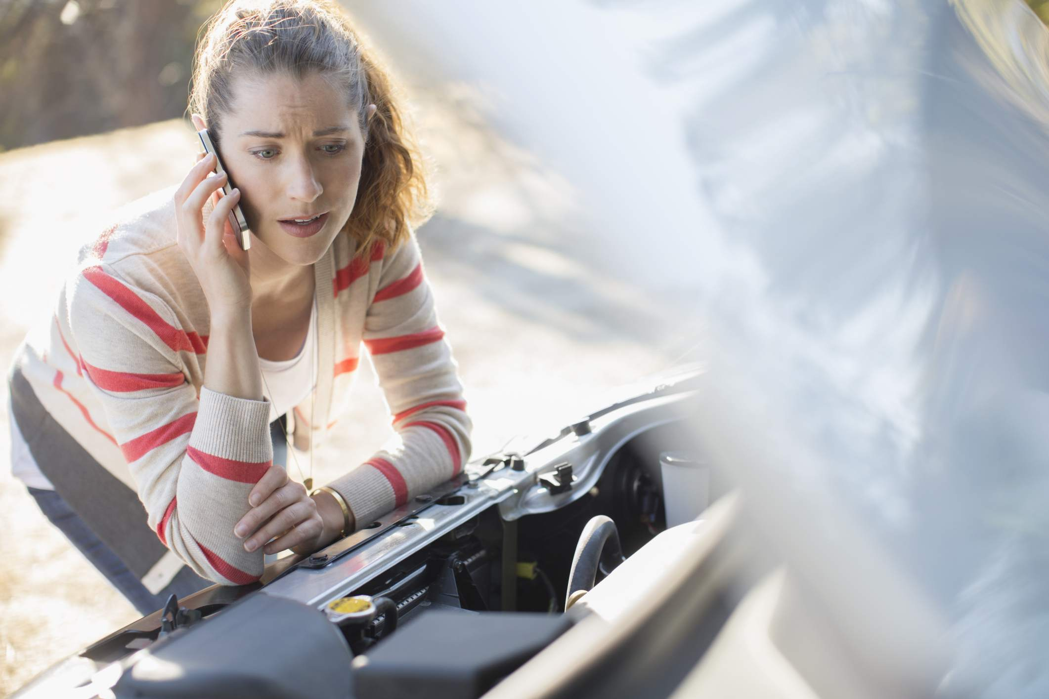 Person on the phone under the hood of broken down car