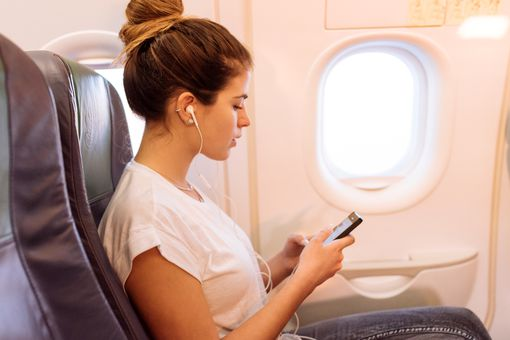 A woman sitting on an airplane listening to a tech podcast on her smartphone.