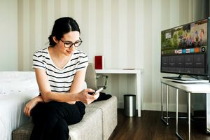 A woman sitting on a bed in a hotel room using the Fire TV iPhone app to control her Amazon Fire TV Stick without a remote.
