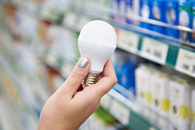 Woman holding LED bulb