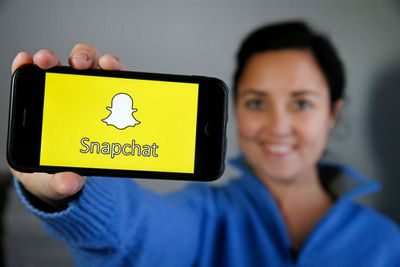 A young person holding a phone out with the Snapchat logo on the screen.