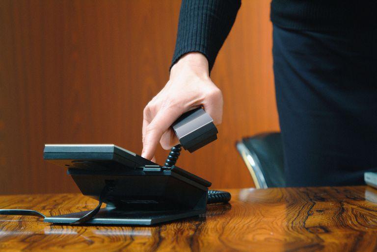 A businessman using a VoIP phone.