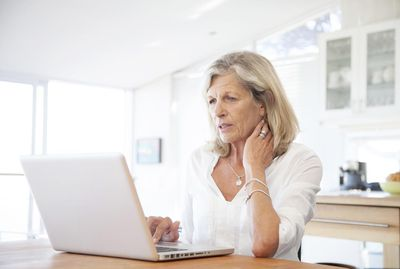 Senior woman working on laptop computer in kitchen