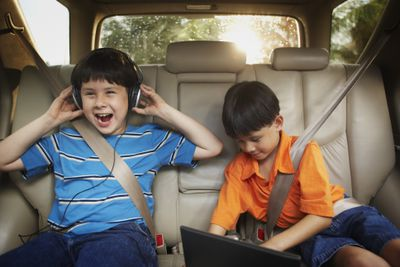 Kids using headphones and laptop in car