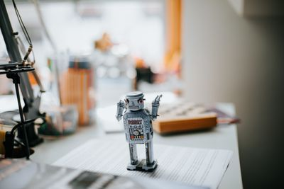 A little tin robot sitting on a desk on top of papers.
