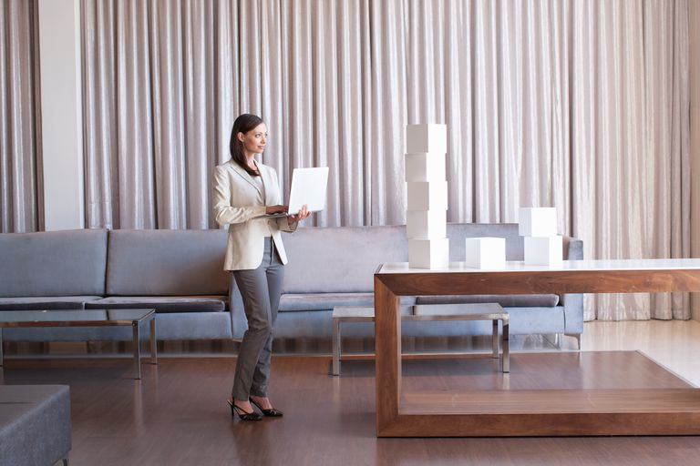 Woman standing with computer looking at blocks on a table