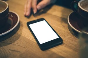 Smartphone and coffee on wooden table