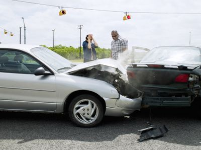 Two people at a car accident at an intersection of the road.