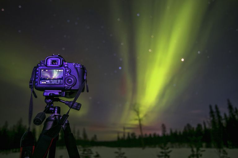 Northern Lights in Sweden being captured by a DSLR camera on a tripod