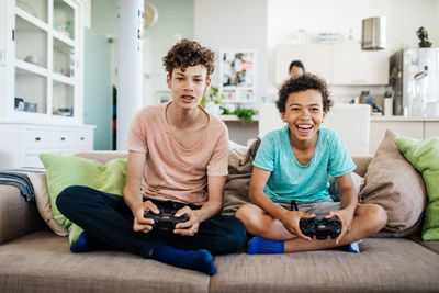 Two boys sitting on a couch smiling with games controllers in their hands