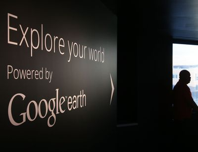 A man stands near a Google Earth exhibit at Google's Washington headquarters