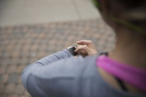 Fitness enthusiast using smart watch while running