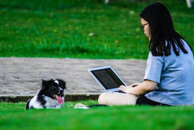 Young woman with dog outside using laptop