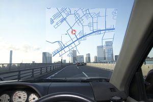 a GPS screen in car windshield, skyline ahead