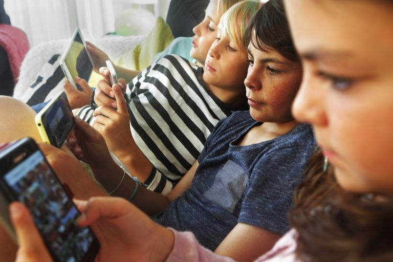 Four children sitting on a couch looking at their smartphones