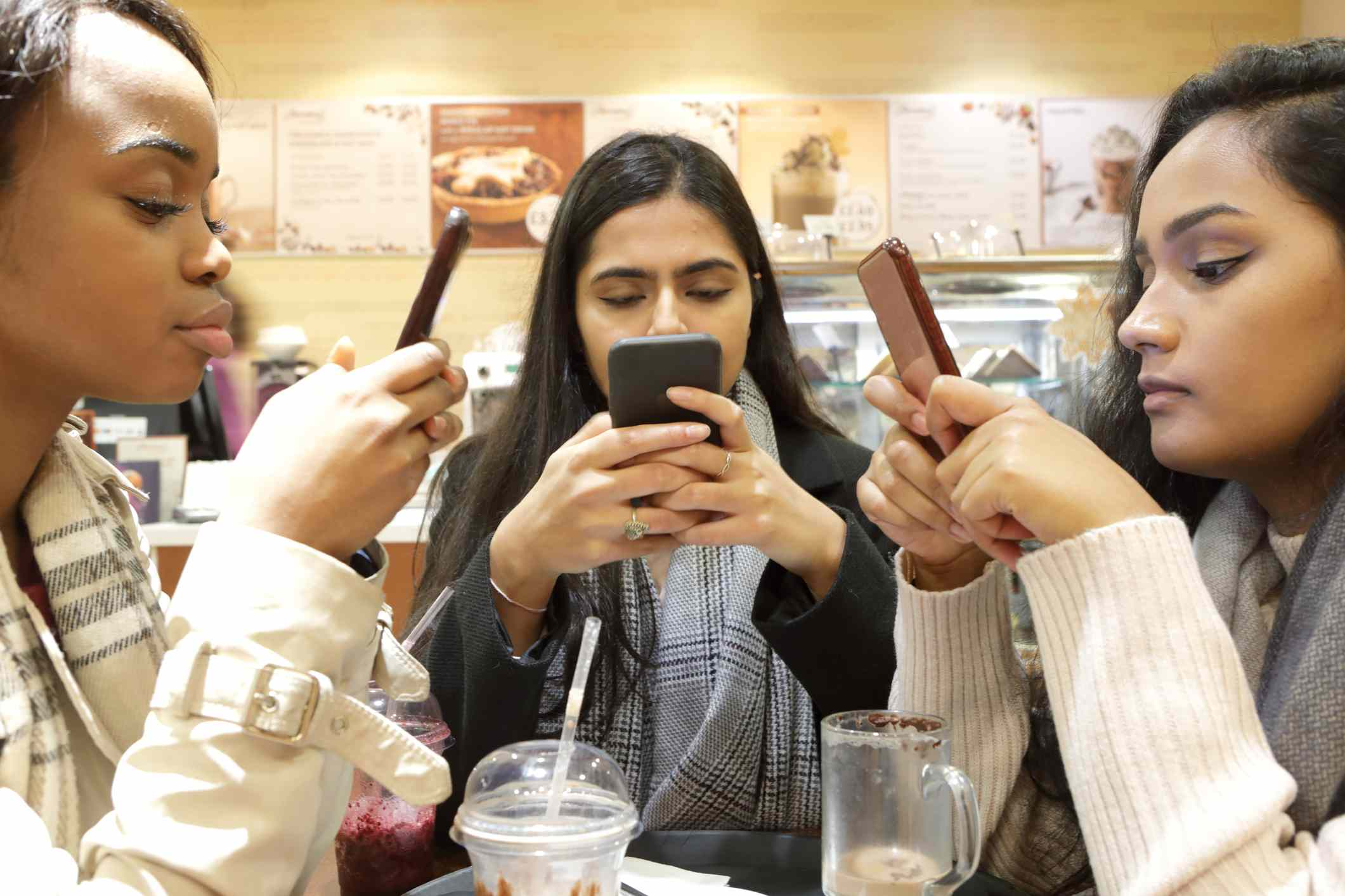 Three woman on phones in cafe