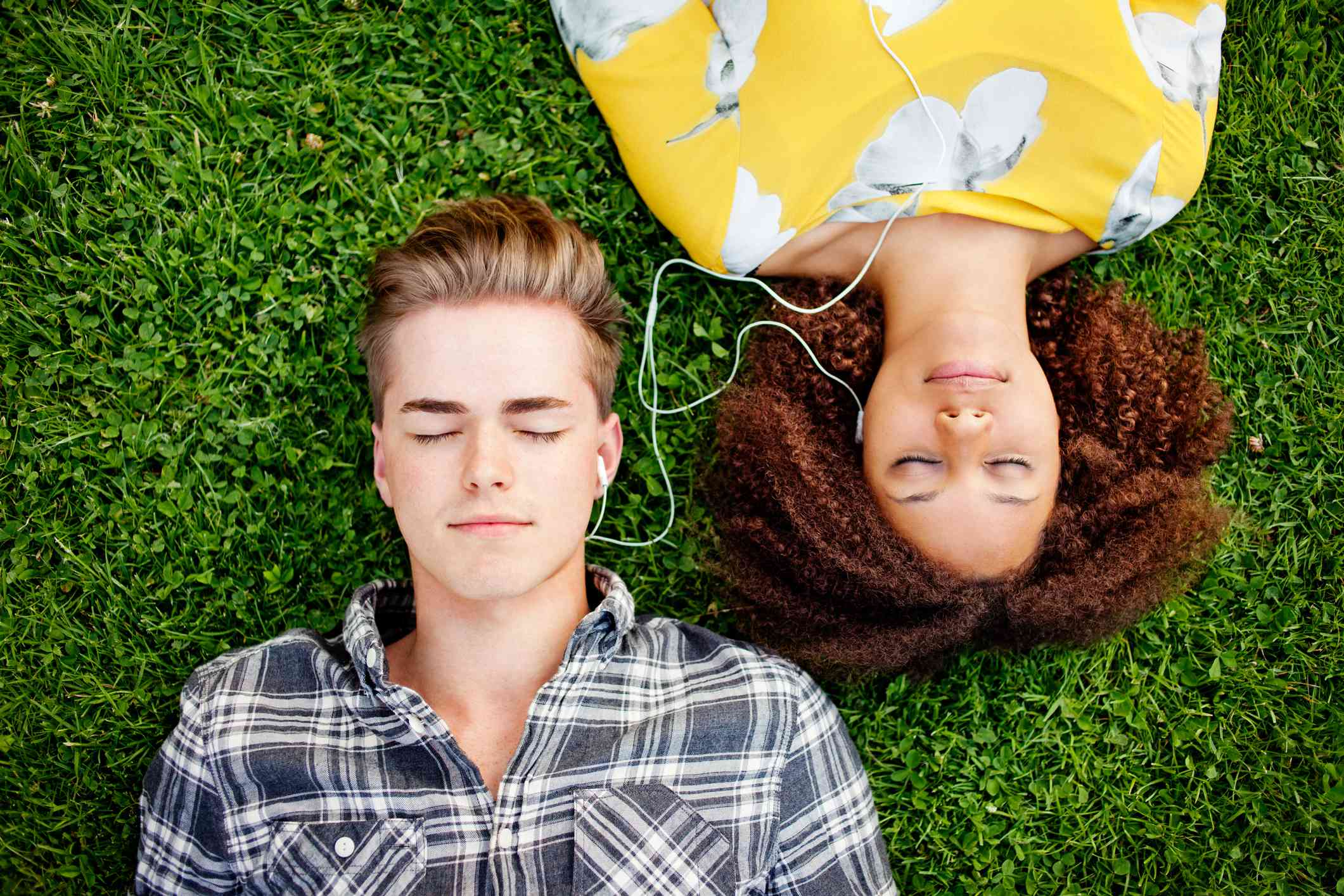 Couple listening to and sharing music while laying on grass