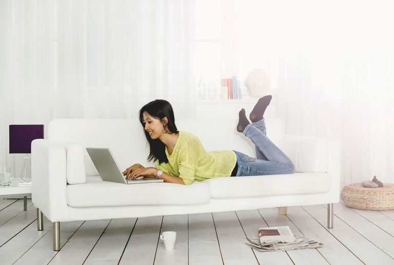 Young woman lying on sofa with laptop computer